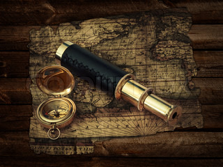 traveling theme: vintage telescope and compass at antique (17 century) map at wooden background
