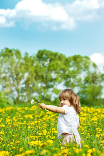 Little girl in a dandelion meadow holding dandelion in the hand