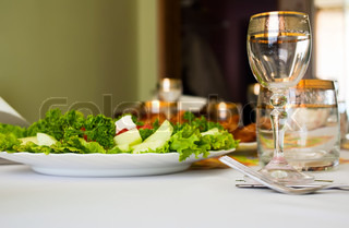 glass and salad on dinner table