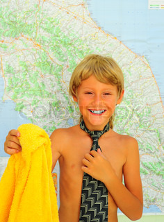 Little Boy With Tie And Bath Towel Near The Map