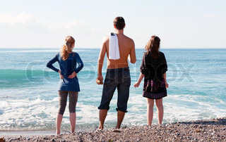 man and two girls looking at the sea