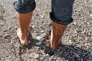 pair of men's feet on the beach with pebbles