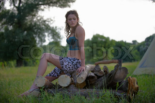 Sexy fresh young woman in nice underclothes with wineglass sitting on the pile of firewood