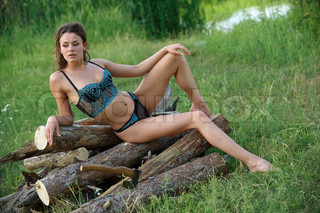Sexy fresh young woman in nice underclothes sitting on the pile of firewood