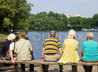 5 old people, sitting on a bench, enjoying the fine weather and the view at the river bank
