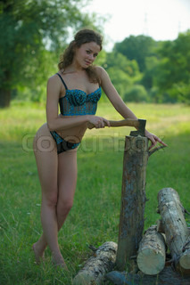 Sexual girl  in nice underclothes chops firewoods on to the meadow