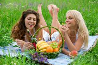 Two attractive girls lie on the rug on the grass beside baskets of fruit and talking