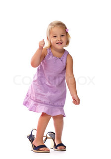 little girl with blond hair in a purple dress standing in  mother's shoes