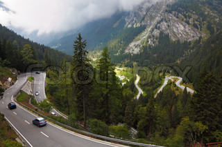 Cars on a steep mountain road turn in the Italian Alps