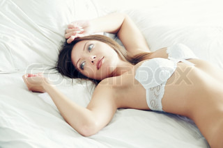 Pretty lady with white camisole laying on the bed at early morning. Natural light and colors
