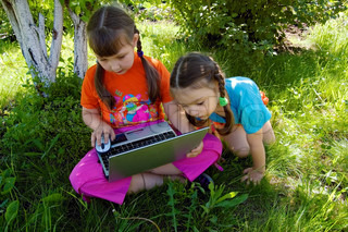 Two girls, seven and three years, with the laptop sitting on the grass under a tree on a sunny day
