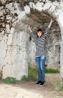 Young girl in jeans in an arch in the ruins