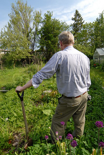 Man leaning on a spade and looking round the overgrown garden vertical