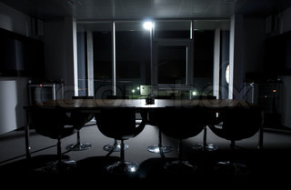 An empty conference room bathed in moonlight