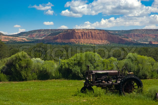 An old tractor left in a field of grass with a magnificient view of an Arizona mountain range