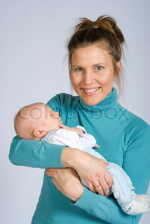 Portrait of a proud young mother holding her newborn son, and smiling to the camera