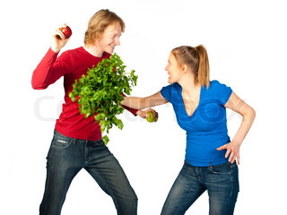 An adult couple fighting for fun with different vegetables
