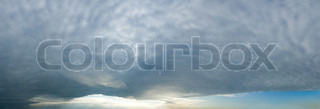 High resolution panorama of an eerie cloud formation of a solid weather front covering most of the sky