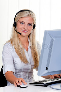 Young woman with headset at computer hotline.