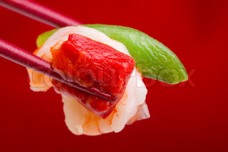 Food from an Asian appetizer in red chopsticks on a red background.