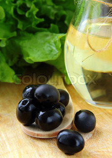black olives and a bottle of olive oil on a wooden table