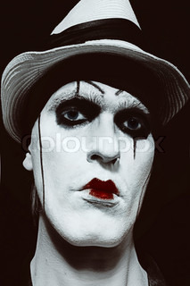 face  of mime with dark make-up on black background closeup