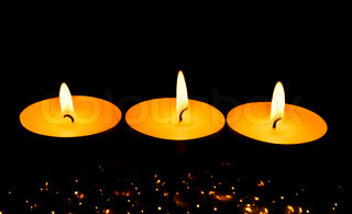 Three candles against a dark background