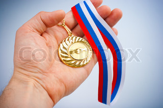 Golden medal with handshake symbol on palm