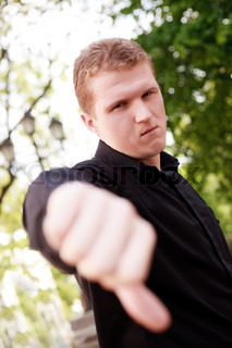Blonde man outdoor with thumb down