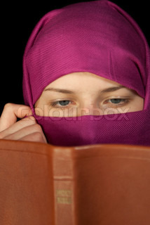 Teen girl muffled in a shawl readingg the Bible