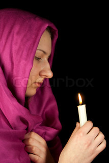 Eastern style dressed teen girl with a candle