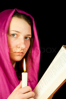 Eastern style dressed teen girl with a candle and the Bible