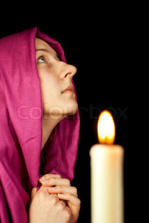 Eastern style dressed teen girl praying with a candle