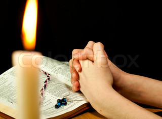 Open Bible with burning candle and hands of praying woman
