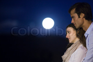 Couple embracing outdoors at night