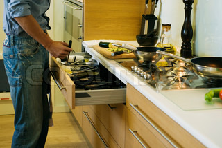 ©Eric Audras/AltoPress/Maxppp ; Man cooking, taking utensil out of drawer
