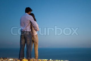 ©Sigrid Olsson/AltoPress/Maxppp ; Couple standing on edge of infinity pool at dusk, looking at sea