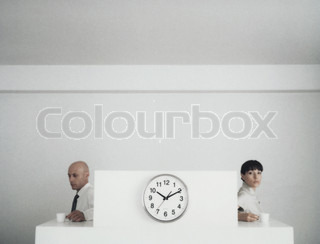 ©Matthieu Spohn/AltoPress/Maxppp ; Woman and man sitting back to back at desks with cups of coffee