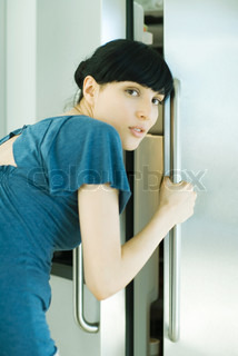 ©Laurence Mouton/AltoPress/Maxppp ; Woman bending over, opening refrigerator, looking over shoulder