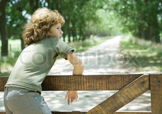 ©Sigrid Olsson/AltoPress/Maxppp ; Boy hanging on fence, dirt road in background