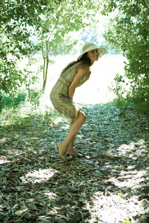 ©Laurence Mouton/AltoPress/Maxppp ; Young woman wearing sundress and sun hat in woods, bending over, full length