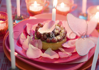 ©Laurence Mouton/AltoPress/Maxppp ; Raspberry pastry on plate decorated with rose petals and candles