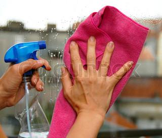 ung kvinde hænder på vinduespudsning et glas