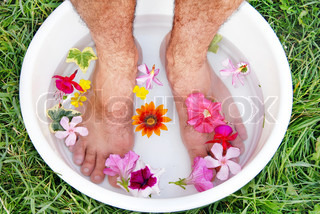 male hairy feet in bowl with water and flowers
