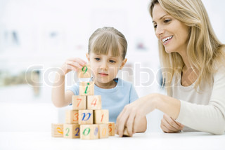 ©Eric Audras/AltoPress/Maxppp ; Little girl stacking blocks, mother watching and smiling