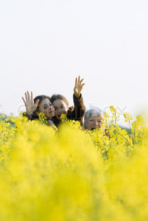 ©Laurence Mouton/AltoPress/Maxppp ; Senior woman and two granddaughters standing in field, waving at camera