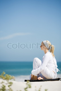 ©Alix Minde/AltoPress/Maxppp ; Young woman sitting on beach with knee up, eyes closed