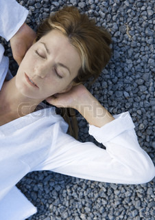 ©Alix Minde/AltoPress/Maxppp ; Woman lying on gravel with hands behind head, eyes closed