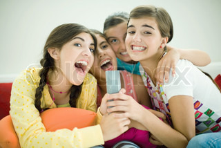 ©Laurence Mouton/AltoPress/Maxppp ; Young female friends sitting together, singing into remote control