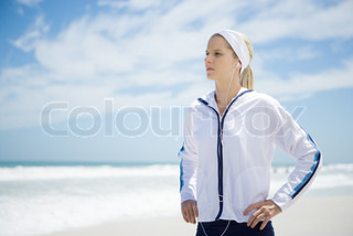 ©Alix Minde/AltoPress/Maxppp ; Young woman in active wear on beach, listening to earphones, hands on hips
